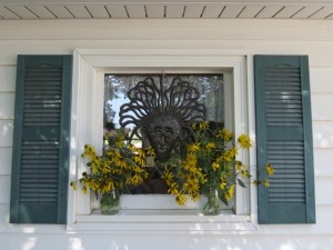 In a window, hung with a hook from the frame, a happy faced mask peeks over the sunflowers.