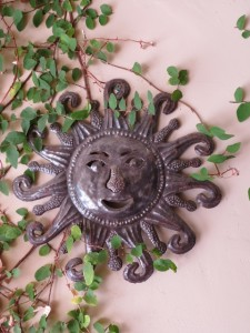 A small sunface with climbing vines hung near a front door can be welcoming.
