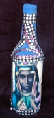 Image of a Black Madonna as Erzulie Freda adorns a sequined bottle from Haiti
