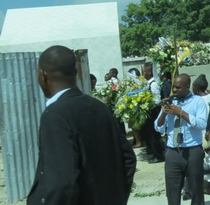 Huge floral arrangements swirled behind the casket as mourners entered the cemetery.