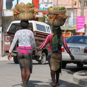 Women headed to market walking in the middle of the street where the sidewalks are too narrow.