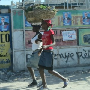 Haitian women stroll past an array of political ads in Port-au-Prince