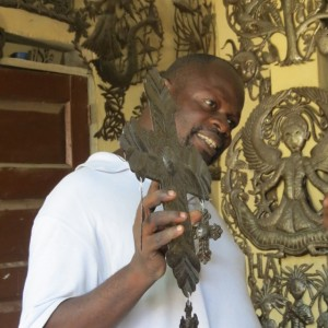 Haitian Metal sculptor, Jean Claude Soulouque with his recycled metal art.